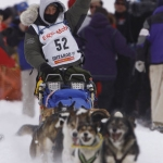 Kim Darst and Dog Team  Waving while Racing